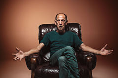 Worried mature man sitting at studio Stock Photo