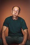 Worried mature man sitting at studio Royalty Free Stock Photography