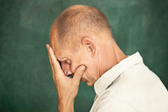 Worried mature man touching his head. Worried mature man touching his head and thinking on studio background Stock Image