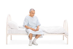 Worried mature patient sitting on a bed stock image