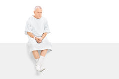 Worried mature patient sitting on a blank panel Stock Photos