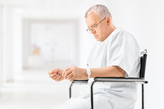 Worried mature patient sitting in a hospital corridor Stock Photos