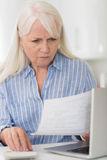 Worried Mature Woman With Laptop Calculating Household Finances Royalty Free Stock Image