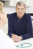 Worried Mature Woman Meeting With Doctor In Surgery Royalty Free Stock Photos