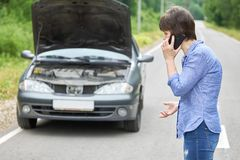 Worried woman talks on the phone near her old broken car on the road. Worried middle-aged woman talks on the phone near her old broken car with raised hood on stock images