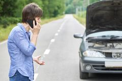 Worried woman talks on the phone near her old broken car on the road. Worried middle-aged woman talks on the phone near her old broken car with raised hood on royalty free stock photos