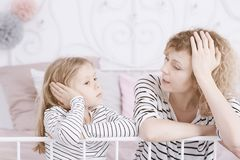 Worried mom and daughter. Sitting on the bed stock images