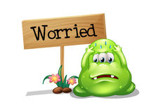 A worried monster beside the wooden signboard Royalty Free Stock Images