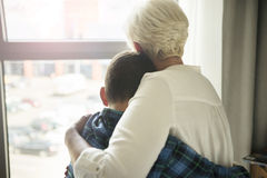 Worried mother cuddling her very sad son. Sitting back Stock Photos