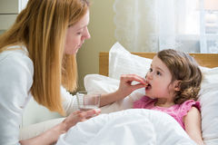 Worried mother giving medicine to her ill kid. Worried mother giving glass of water to her ill kid. Sick child with high fever laying in bed and taking a Royalty Free Stock Photo