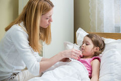 Worried mother giving medicine to her ill kid stock photo