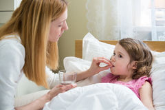 Worried mother giving medicine to her ill kid. Worried mother giving glass of water to her ill kid. Sick child with high fever laying in bed and taking a Royalty Free Stock Photos