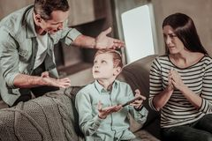 Worried mother looking at her son and husband. Want to play. Serious men actively gesticulating while talking to his kid royalty free stock images