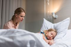 Worried mother looking at sick kid sleeping on bed. In hospital stock photos