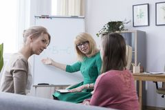 Introverted daughter visiting child psychologist. Worried mother and young introverted daughter visiting child psychologist, therapist helping teenage girl to Royalty Free Stock Image