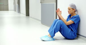 Worried nurse sitting on the floor