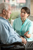 Worried nurse. Young worried nurse talking with with older man Stock Image