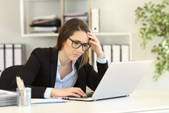 Worried office worker reading bad online news. In a laptop royalty free stock image