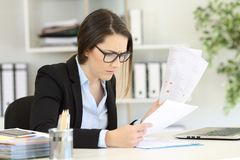 Worried office worker reading sales reports. Sitting in a desktop at workplace royalty free stock photography