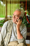 Worried old man. Aged man using cellphone, looking anxious after some bad news Royalty Free Stock Images