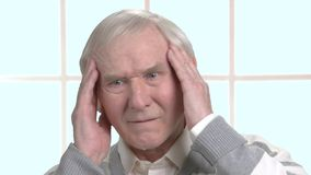 Worried old man massaging his temples. Sad elderly man having strong headache, window background. Human health problems and facial expressions stock footage