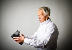 Old man in white and empty wallet. Worried old man in white is looking at an empty wallet Royalty Free Stock Photos