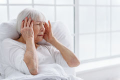 Worried old woman has headache in hospital Royalty Free Stock Images