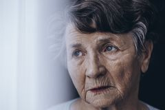 Worried old woman`s face. Close-up of worried, lonely old woman`s face with wrinkles royalty free stock photography
