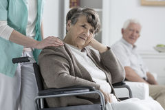 Worried older woman. Worried older women on a wheelchair in a nursing home Stock Image