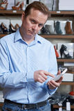 Worried Owner Of Shoe Business With Calculator. Worried Male Owner Of Shoe Store With Calculator Royalty Free Stock Images