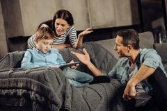 Worried parents yelling at their son for binge-playing. Heated quarrel. Worried upset parents yelling at their son, convincing him to stop binge-playing on the stock photo