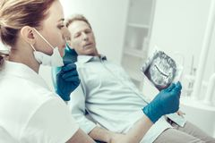 Worried patient looking at the dentist with his X-ray Royalty Free Stock Photography