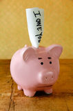 Worried Piggy Bank. With an IOU note Stock Images