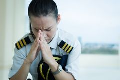 Stressed out female pilot worried at work royalty free stock image