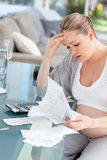 Worried pregnant woman calculating her bills Stock Image