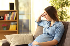 Worried pregnant woman at home. Worried pregnant woman sitting on a couch in the living room at home Stock Photos