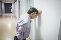Worried professor leaning on wall. In corridor royalty free stock photo