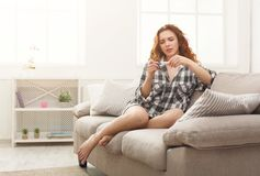 Worried girl reading the results of her pregnancy test. Worried redhead girl checking her recent pregnancy test, sitting on beige couch at home royalty free stock image