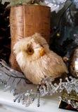 Worried regardant le hibou de Noël par la bougie de bouleau avec les décorations argentées sur le manteau Photographie stock libre de droits