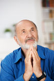 Worried religious senior man praying. To god with his hands raised and touching as he looks beseechingly towards heaven for help and inspiration royalty free stock photo
