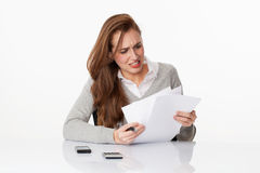 Worried 20s woman classifying administrative documents in office Royalty Free Stock Images