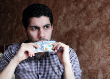 Worried sad arab young businessman with dollar bill. Arab young muslim business man feeling sad and confused with dollar bills in his hand and thinking Stock Photography