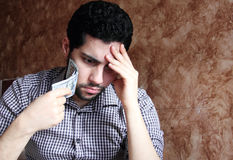 Worried sad arab young businessman with dollar bill. Arab young muslim business man feeling sad and confused with dollar bills in his hand and thinking Royalty Free Stock Photos