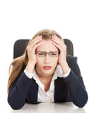 Worried, sad business woman sitting by the table. Royalty Free Stock Image