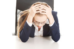 Worried, sad business woman sitting by the table. Stock Photos