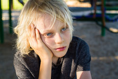 Worried, sad child alone in school playground Stock Photos