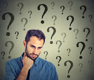 Worried sad man has many questions looking down Stock Image