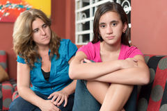 Worried and sad mother looks at her teen daughter Stock Photo