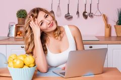 Worried and sad student female searching information in a laptop online sitting in the kitchen. Sad blonde woman feeling royalty free stock images