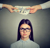 Worried sad woman looking up at hands exchanging money. Worried sad woman looking up at two hands exchanging money stock photo